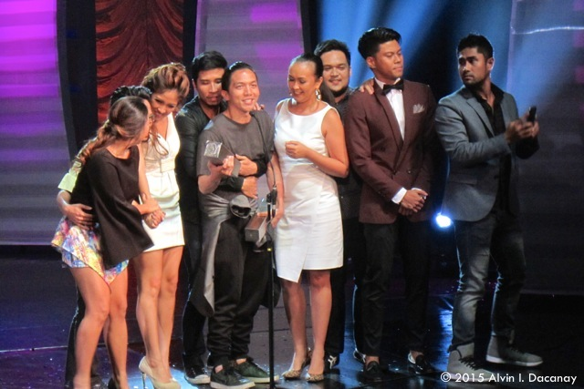 """Rak of Aegis"" choreographer Gio Gahol accepts the Outstanding Ensemble Performance in a Musical prize as some cast members, including Pepe Herrera (behind Gahol), Kalila Aguilos (fourth from right), Jerald Napoles (second from right) and Myke Salomon (far right), listen."