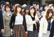 Commuters cross a street during morning rush hour in Tokyo. The central government exceeded its 30-percent target for the hiring of women for career-track positions, raising the rate to 34 percent this year from 24 percent last year, according to the latest Cabinet Office data. AP