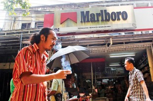 A man smokes a cigarette as he walks past a shop displaying a Marlboro sign at a market in Jakarta, Indonesia. AP