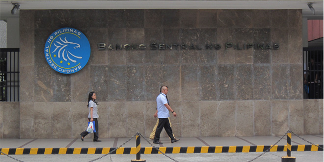 People pass by the Bangko Sentral ng Pilipinas sign at the central bank's headquarters in Malate, Manila. (Photo: Alvin I. Dacanay)