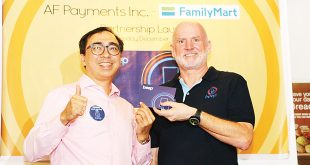 Philippine Family Mart CVS Inc. President and General Manager Manuel C. Alberto (left) and AF Payments Inc. President and CEO Peter Maher hold up a box containing a beep card during the launch of their partnership at the Family Mart flagship store in Glorietta 3, Ayala Center, Makati City, on December 7. (Photo: Alvin I. Dacanay)
