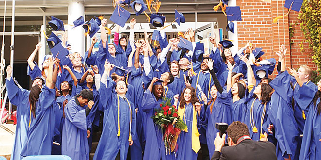 Graduates do the traditional graduation-cap toss. (via Wikimedia Commons)
