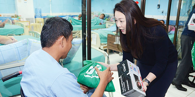 SMFI Executive Director Debbie Sy speaks to a wounded soldier as she hands him a bag of personal hygiene products and radio.