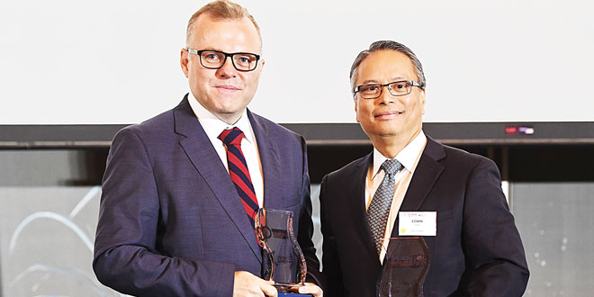 Edwin Reyes (right), Banco de Oro Unibank (BDO) Transaction Banking Group head, poses with the Corporate Social Responsibility (CSR) Program of the Year Gold Award he accepted on the BDO Foundation's behalf at the 2017 Retail Banking Awards in Singapore.