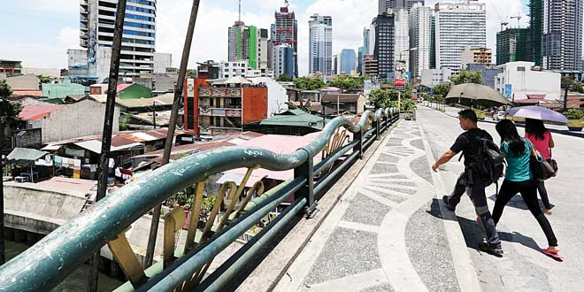 Pedestrians cross over the Pasig River in the City of Makati. The robust economy gets strong support from transfers of Filipinos working overseas estimated at $2 billion a month. (WORLD BANK PHOTO)